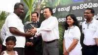 Officials present a plantlet to a local farmer